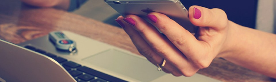 feminine hands working at laptop and holding mobile phone