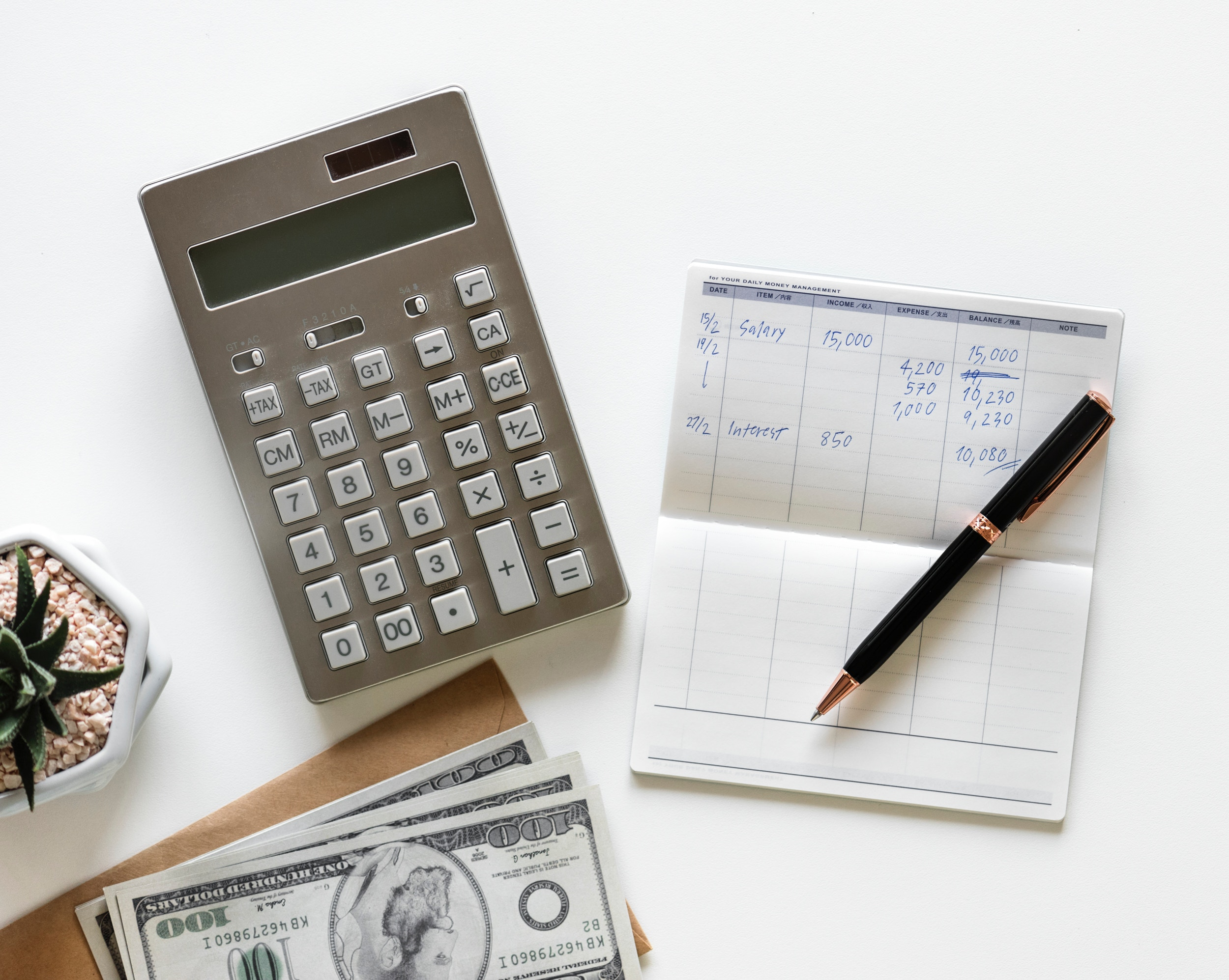 Checkbook register with pen, calculator, and cash on a desk